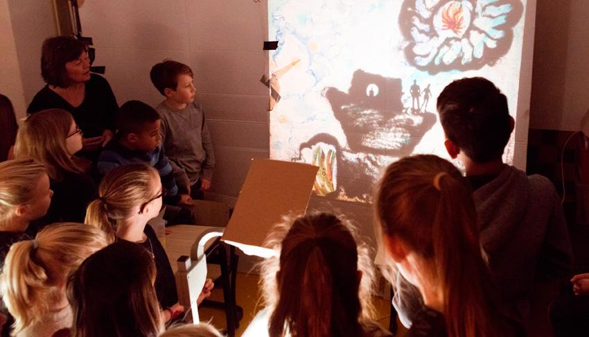 Kids are creating light art with a projector
