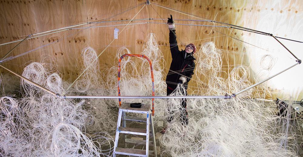 Een vrijwilliger helpt mee met het realiseren van een kunstwerk.